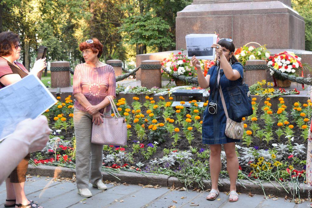 Подножие памятника, клумба с цветами, люди