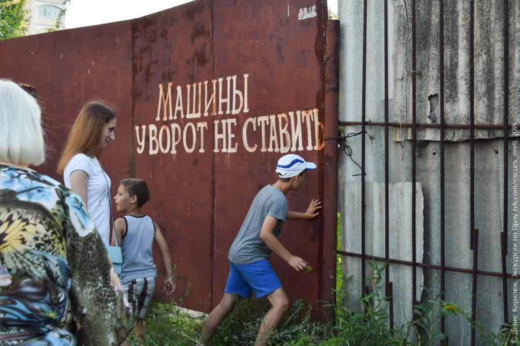Закрытые ворота и любопытный экскурсант, надпись «Машины у ворот не ставить»