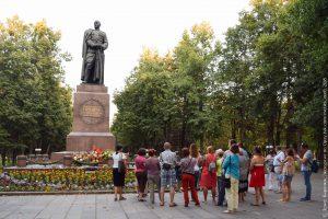 Памятник советскому генералу на высоком постаменте и экскурсанты