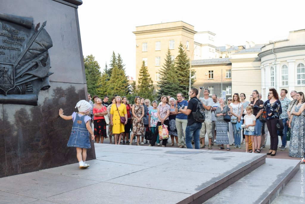 Экскурсанты смотрят на стелу, маленькая девочка подглядывает за экскурсантами