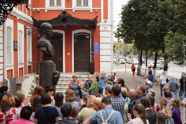 Экскурсанты на фоне здания с чугунным крыльцом и бюст Великого князя