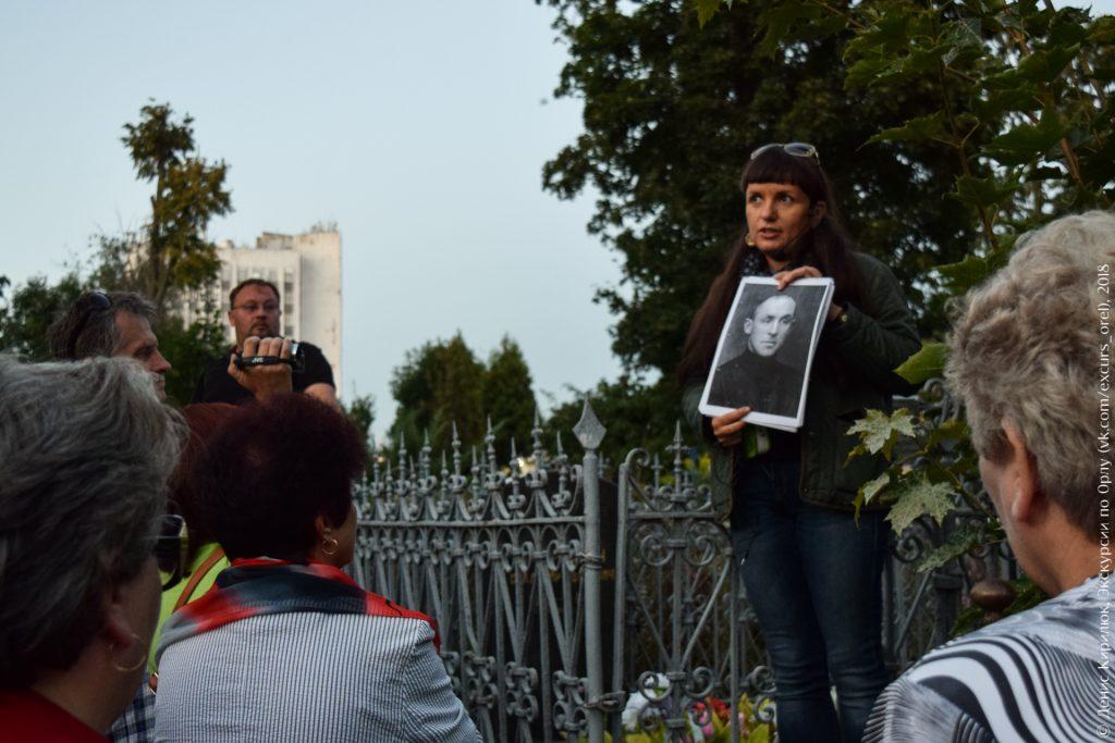 Экскурсовод показывает фото человека у его могилы