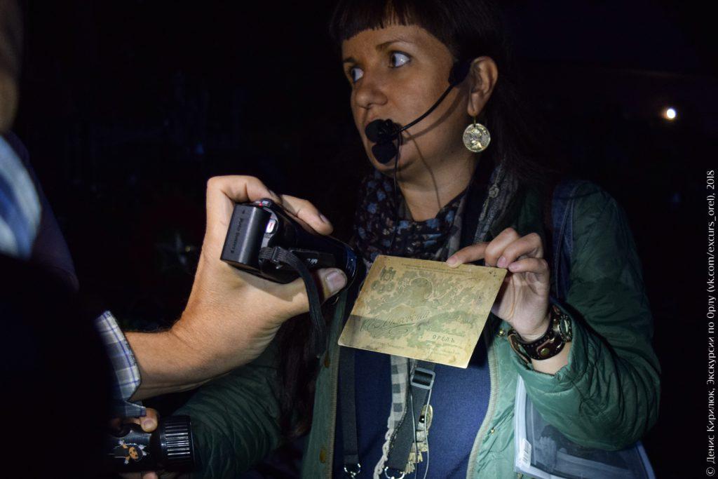 Экскурсовод показывает старую фотокарточку подсвечивая себе фонариком