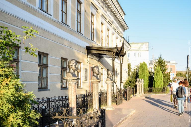 Шесть бюстов на цилиндрических постаментах перед зданием в классическом стиле.