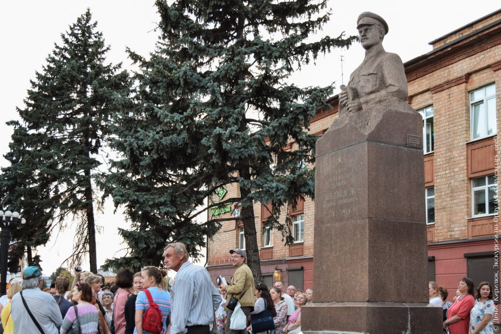 Поясной гранитный памятник военному на фоне заводоуправления