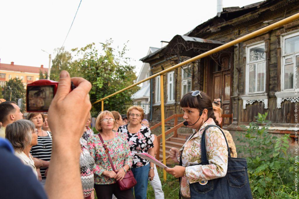 Экскурсанты на фоне старого деревянного дома с кованным козырьком