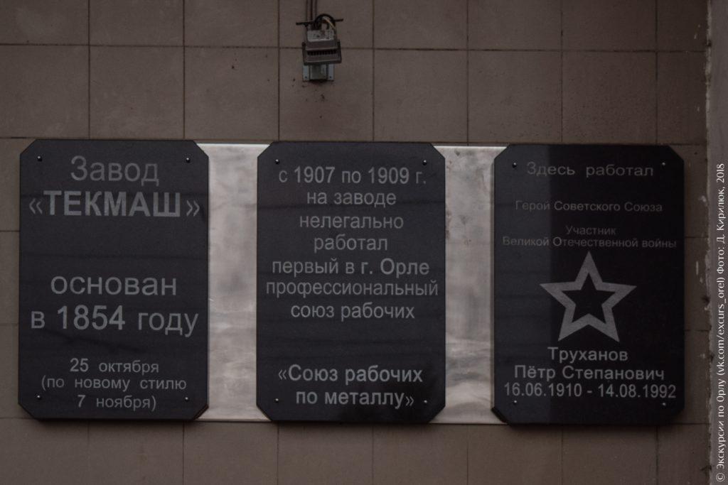 Мемориальные доски завода «Текмаш»: «основан в 1854 году», «с 1907 по 1909 на заводе нелегально работал первый в Орле профсоюз», «здесь работал Герой Советского союза Труханов Пётр Степанович»