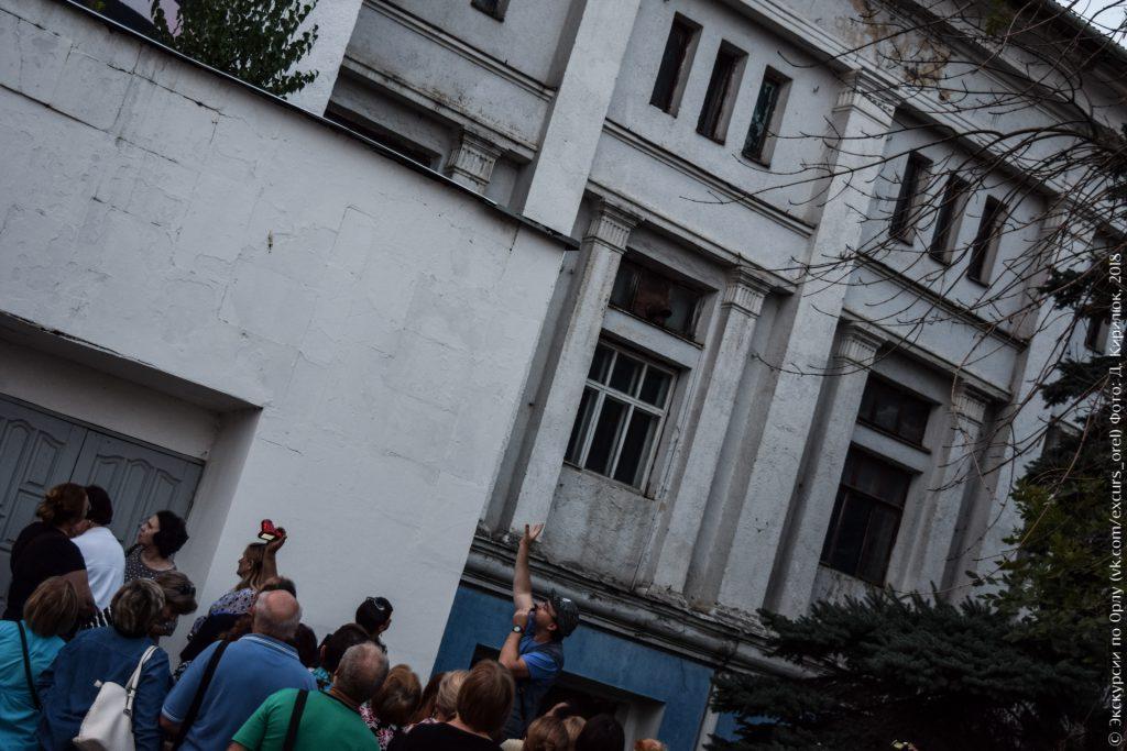 Экскурсовод показывает на здание в стиле конструктивизм