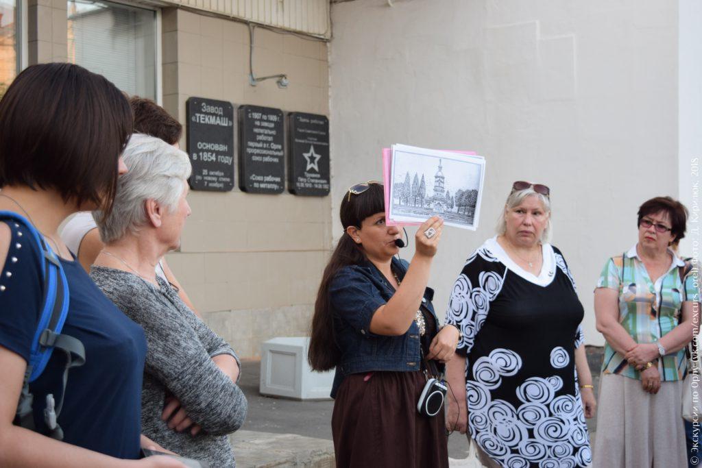 Экскурсовод на фоне проходной завода с рисунком церкви в руке