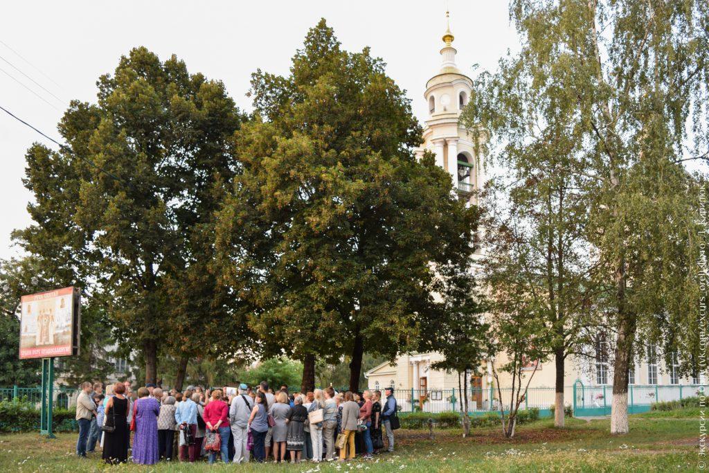Церковь с колокольней в классическом стиле, деревья и экскурсанты