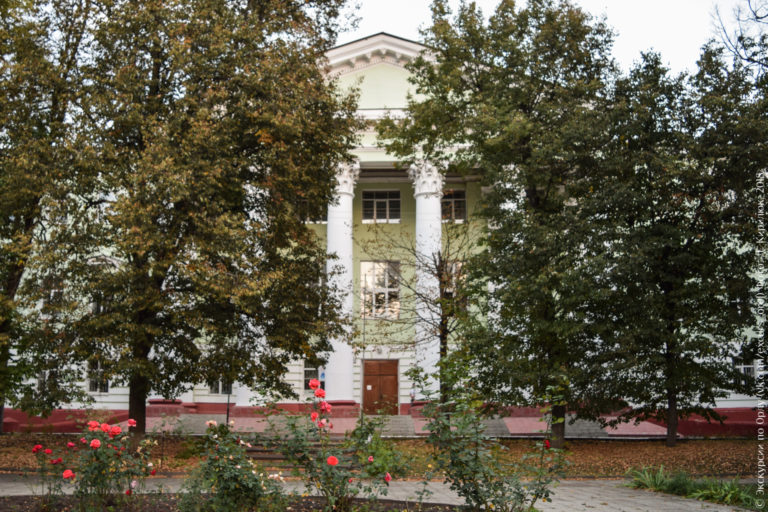 Здание с коринфским портиком за высокими деревьями