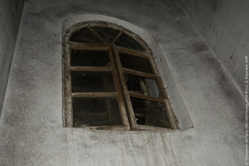 Затемнённое арочное окно на грязной оштукатуренной стене