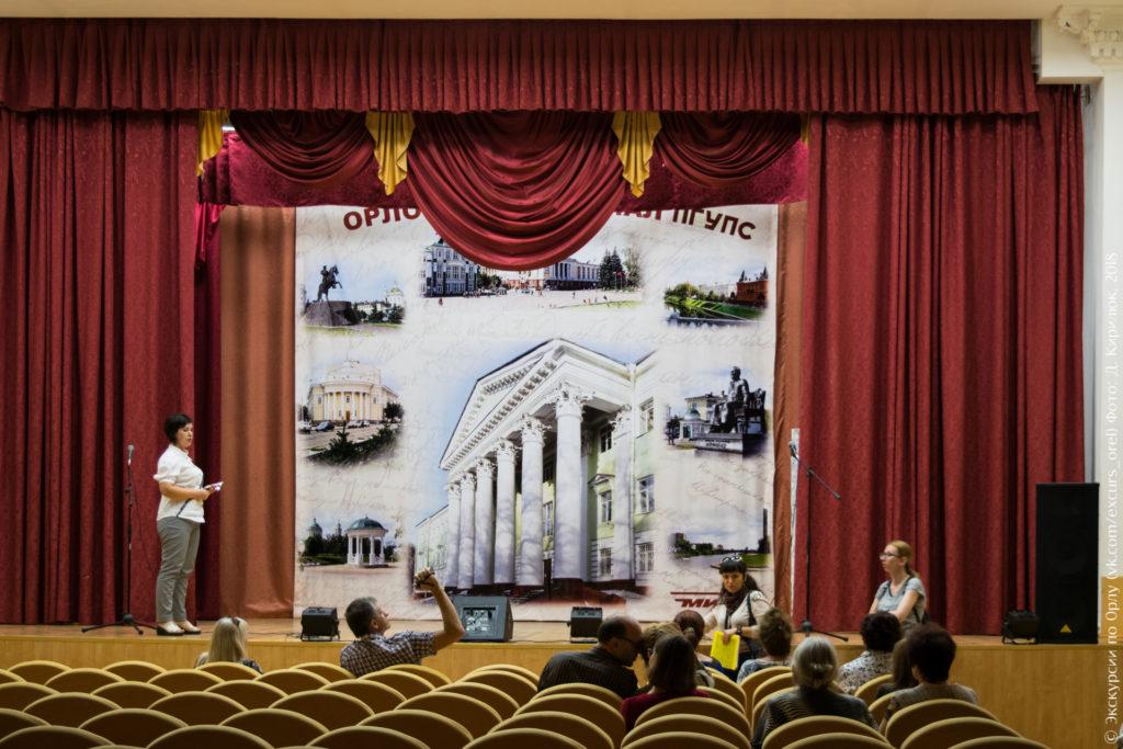 Сцена с красным занавесом и с изображениями памятников Орла