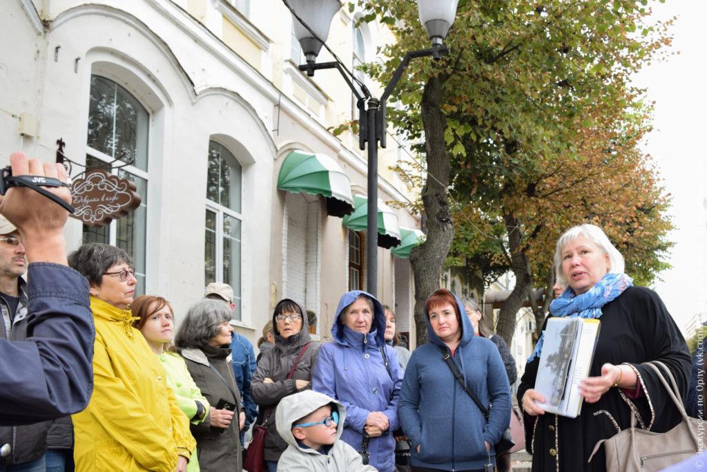 Экскурсанты на фоне дореволюционного дома с арочными окнами