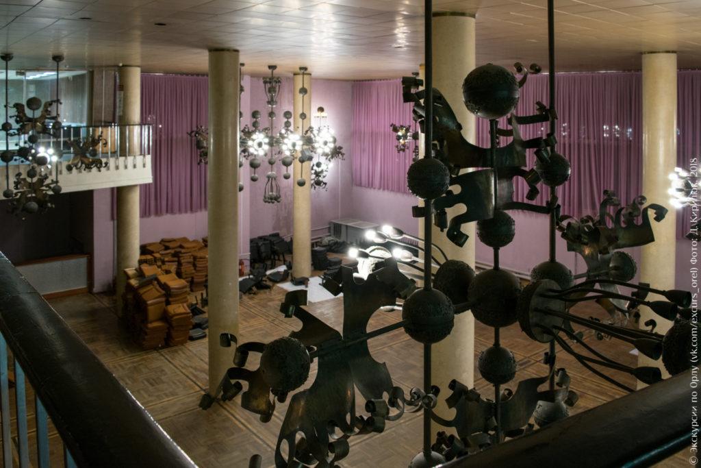 Большие люстры сложной конструкции над актовым залом с колоннами