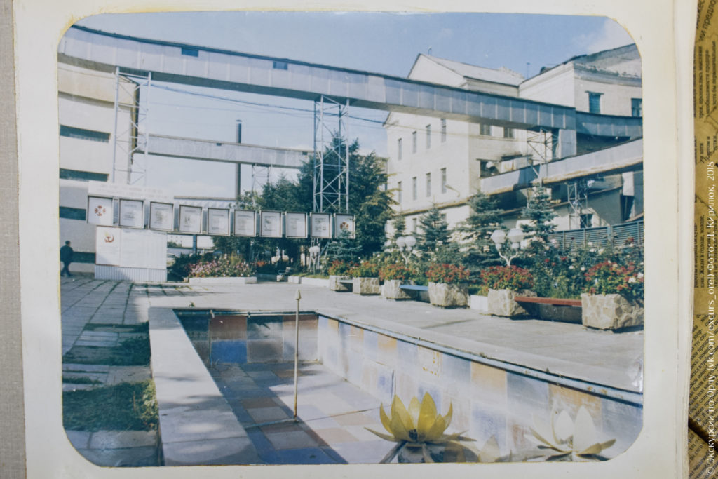 Советский завод с надземными переходами, доской почета, цветами и фонтаном