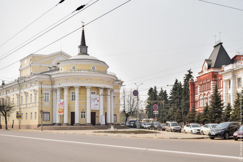 Желтое здание с белой лепниной, с полуротондой, театральной коробкой и афишами между колоннами.