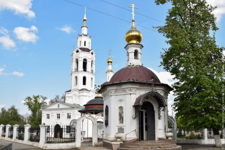 Маленькая часовня с белыми стенами и золотой главкой на фоне церкви с высокой колокольней в том же стиле.
