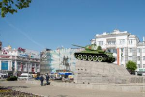 Зеленый танк с красной звездой на гранитном постаменте на фоне украшенных зданий.