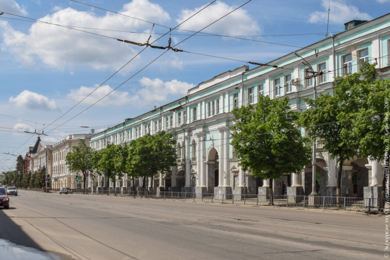 Бирюзовое здание с белыми колоннами и мраморным цоколем, частично закрытое деревьями.