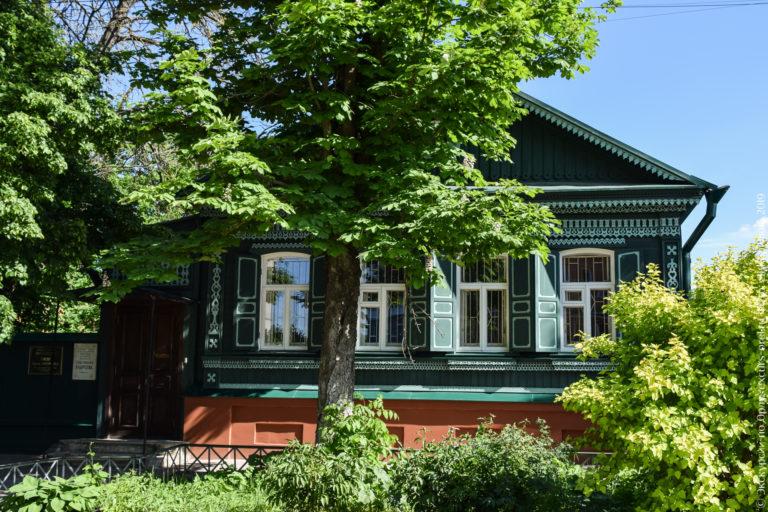 Деревянный темно-зеленый одноэтажный дом с 4 окнами по фасаду, верандой, богато украшен новой резьбой.