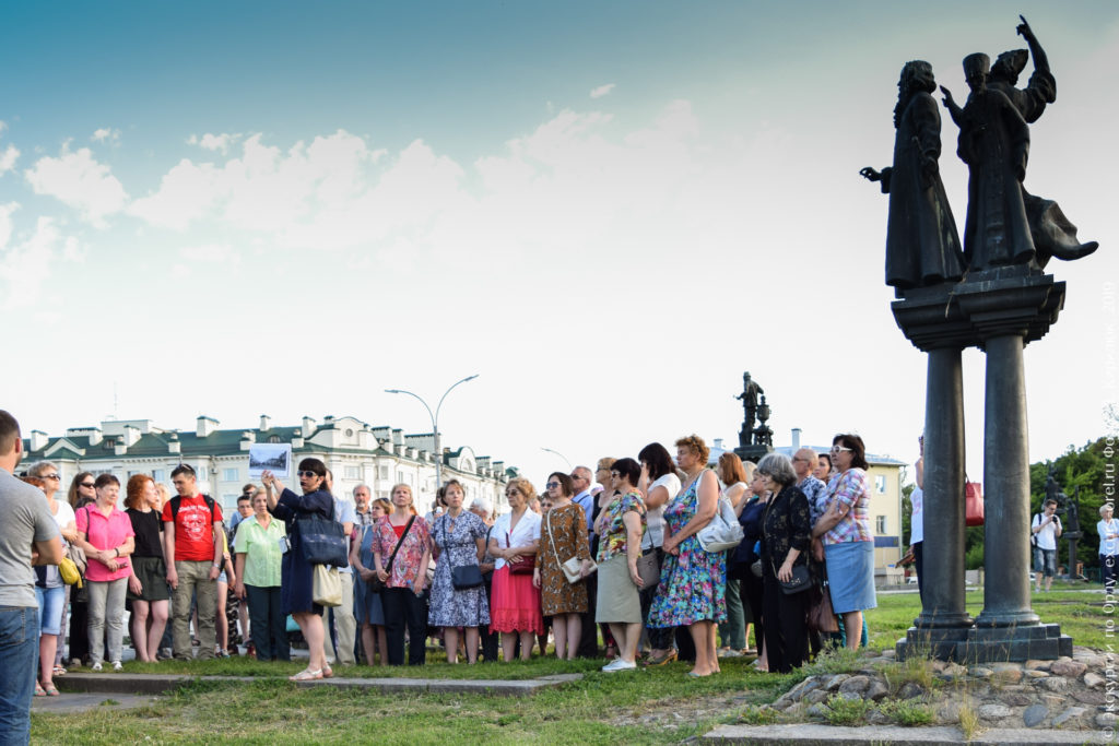 Экскурсанты в окружении скульптур на колоннах.