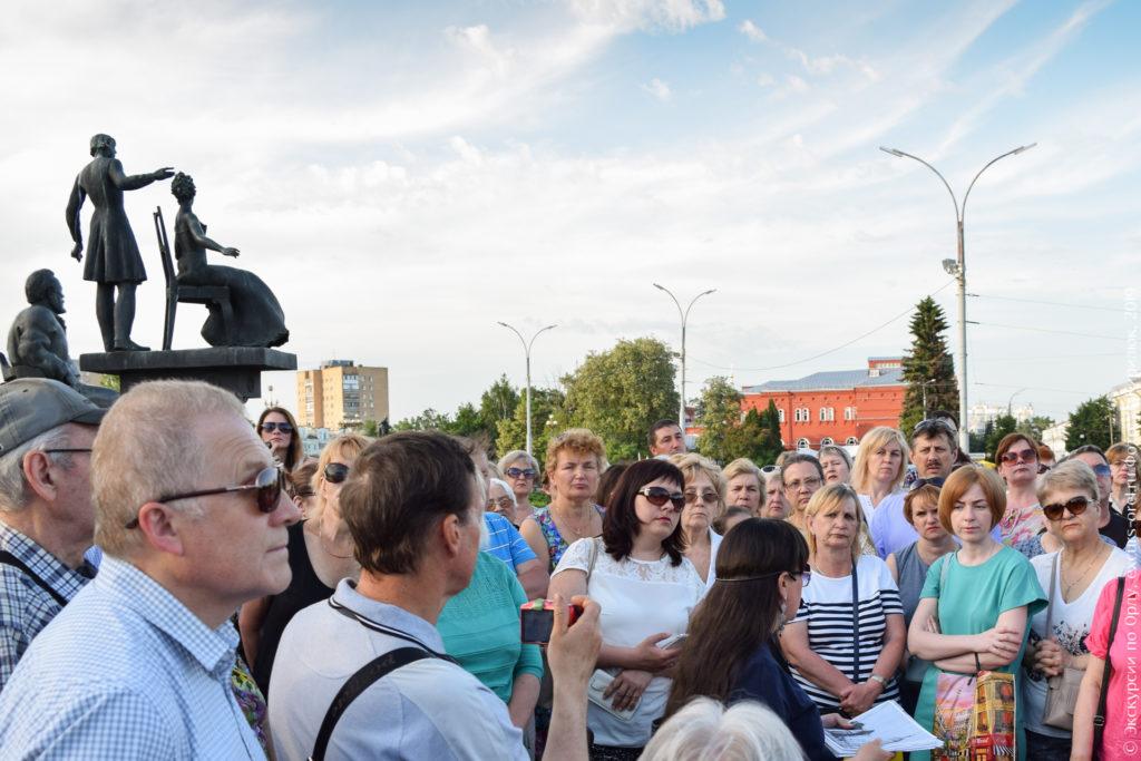 Экскурсанты на фоне памятника Лескову и красного здания банка.