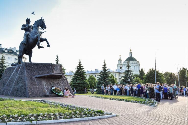 Конный памятник генералу Ермолову и экскурсанты на фоне классической церкви.