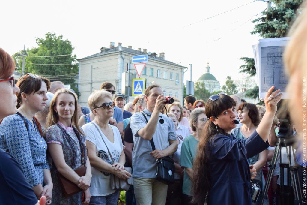 Экскурсанты на фоне кирпичного дома и купола церкви.