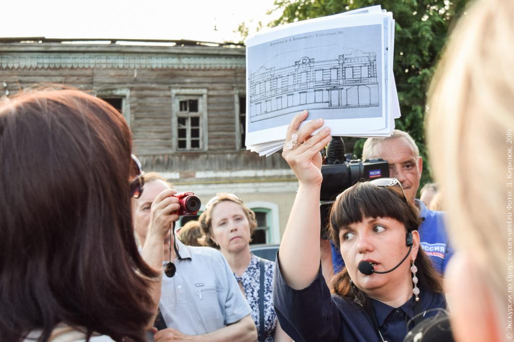 Экскурсовод показывает проект дома на фоне самого дома.