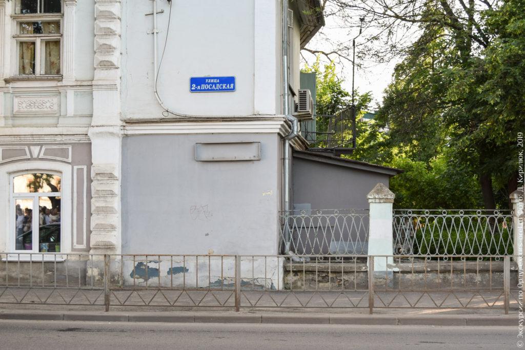 Кованная ограда около дореволюционного кирпичного дома.