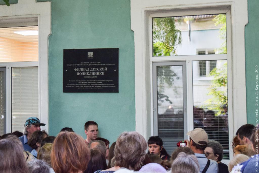 Черная мемориальная доска на зеленой стене.
