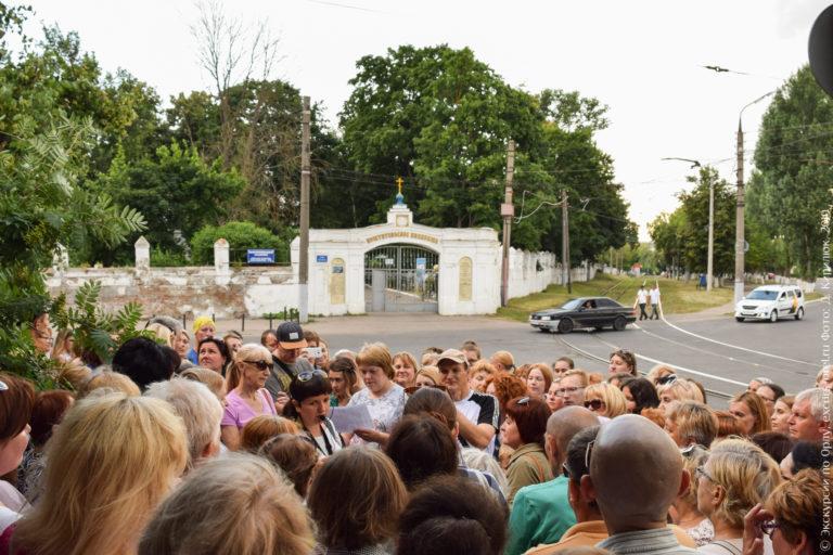 Экскурсанты на фоне кладбищенской ограды и трамвайных путей.