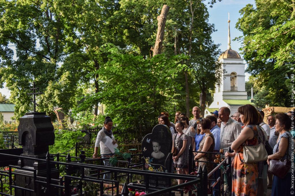 Экскурсанты на кладбище на фоне барочной церкви.