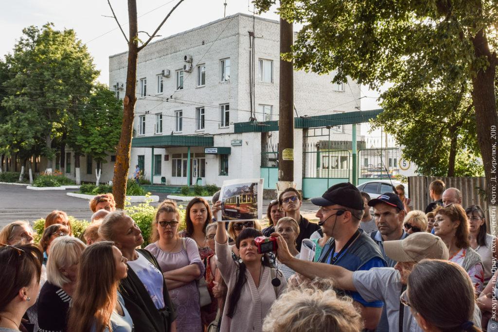 Экскурсанты на фоне 3-этажного кирпичного здания и больших автоматических ворот.
