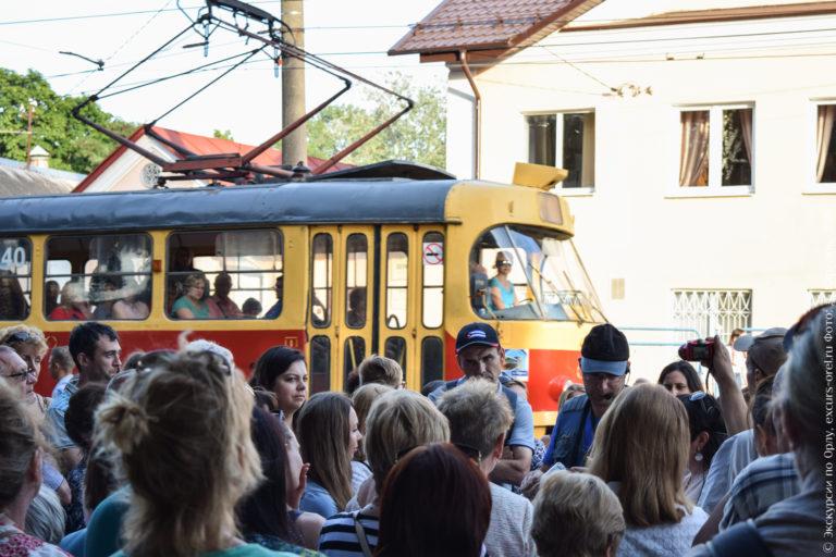 Экскурсанты на фоне проезжающего рядом трамвая.