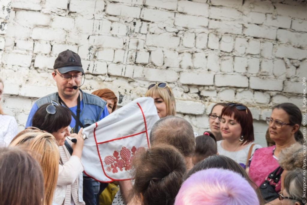Экскурсовод показывает фартук с оригинальной вышивкой.