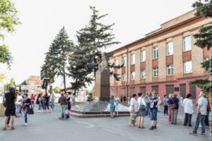 Экскурсанты вокруг поясного памятника военному на фоне заводоуправления.