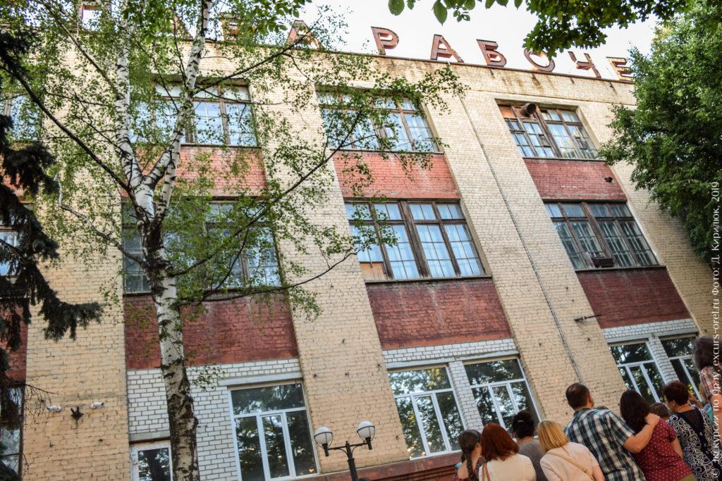 """Заводское здание с надписью """"Слава рабочему..."""" на крыше."""