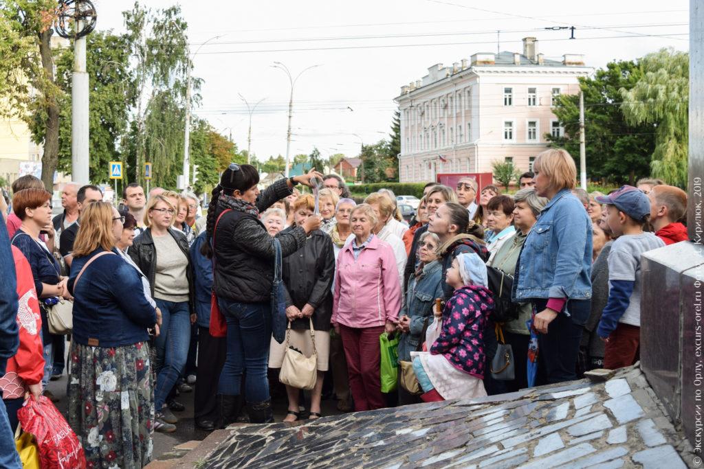 Экскурсанты у постамента памятника на фоне створа улицы и розовой 3-этажной сталинки.