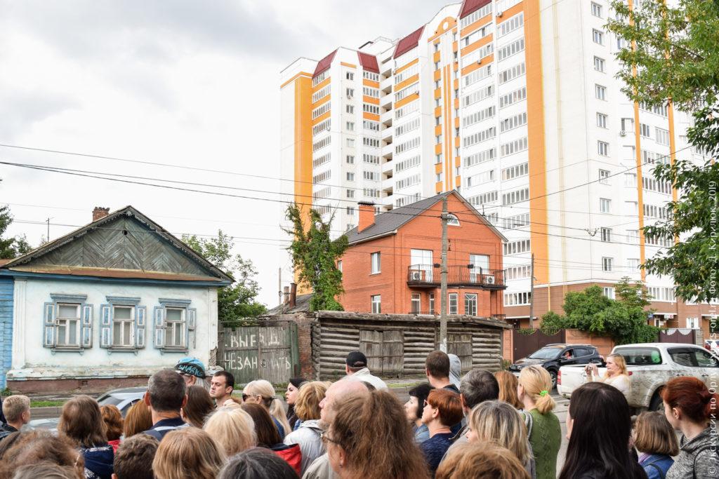 Сруб без крыши с большими воротами на фоне высокой новостройки.