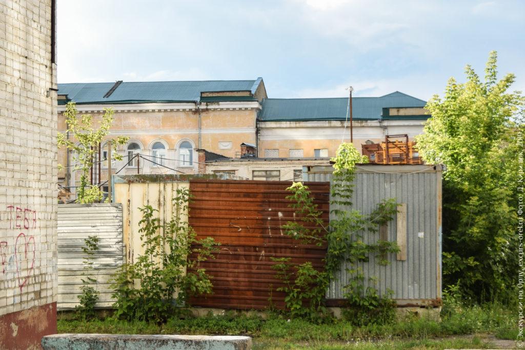Здание с арочными окнами за металлическим забором, заросшим кустами.