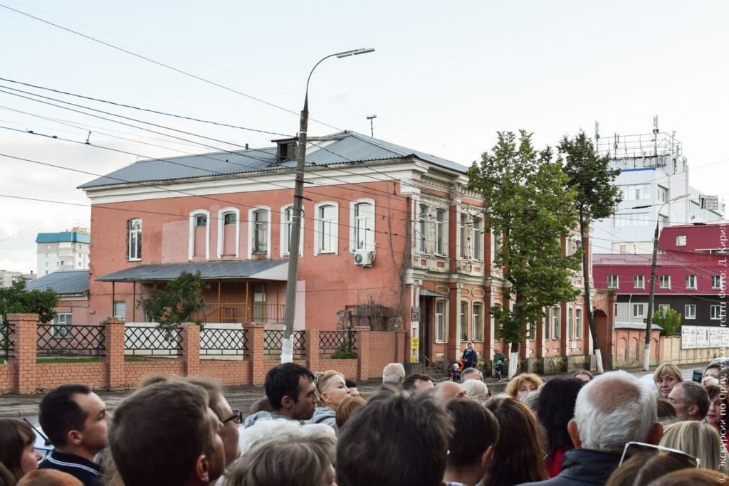 2-этажное красное каменное здание, украшенное белой лепниной в виде женских фигур.