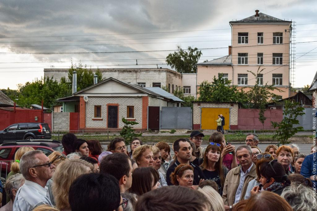 Экскурсанты на фоне 4-этажного школьного здания.