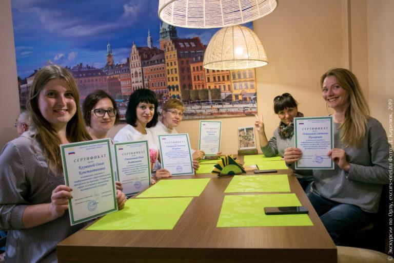 Девушки разных возрастов демонстрируют сертификаты, в кафе.