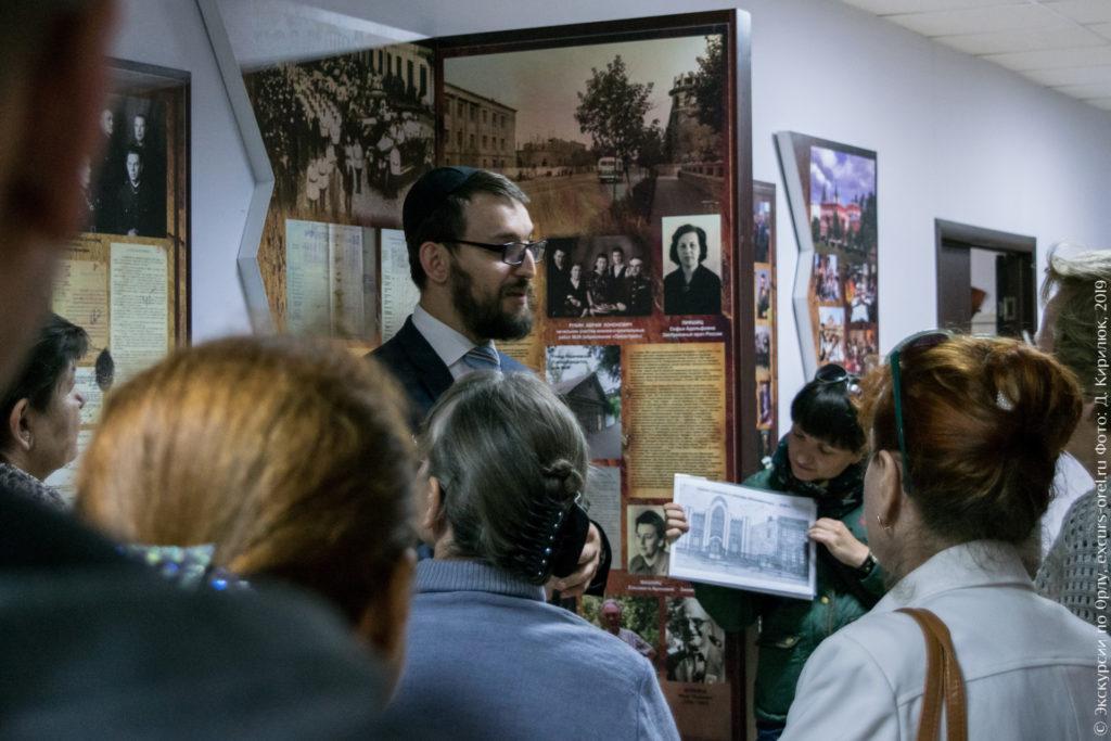 Раввин на фоне информационных стендов и старого рисунка с изображением синагоги.