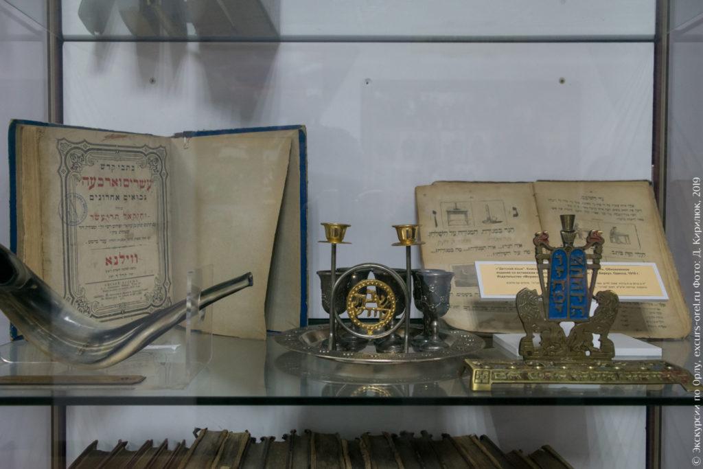 Старые книги на иврите, выделанный рог, металлические ритуальные предметы.