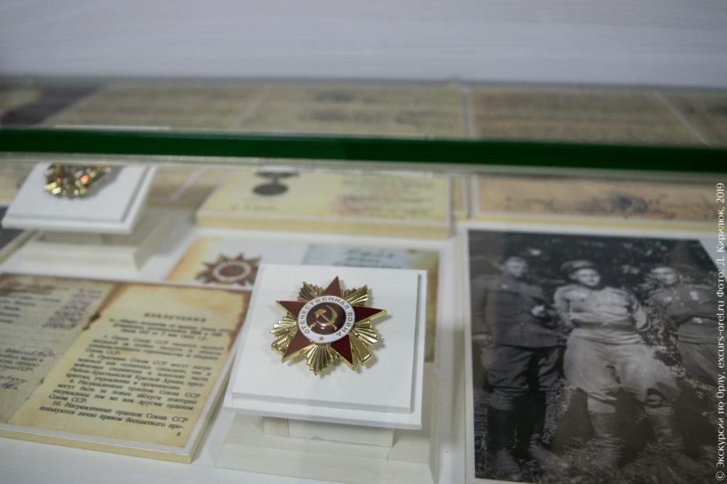 Орден Отечественной войны в витрине в окружении наградных листов и фотографий военных.
