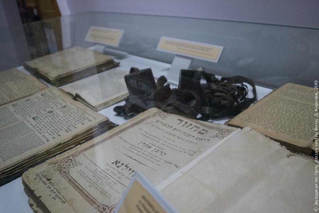 Витрина со старыми книгами на иврите и черными коробочками с ремешками.