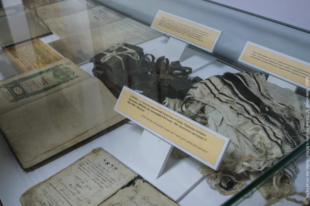 Черные коробочки с ремешками, белый с черными полосками кусок ткани, книги на иврите.
